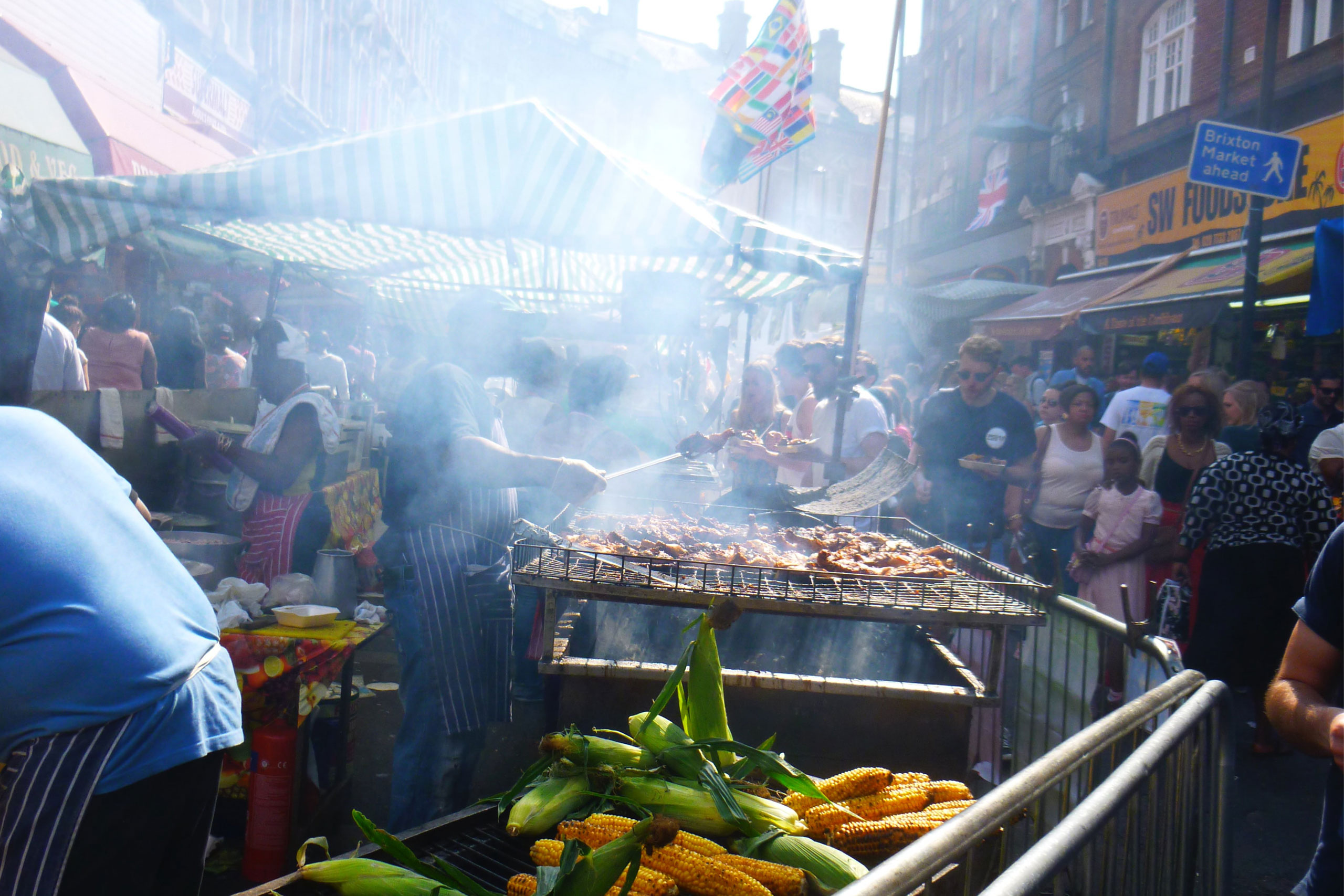 Brixton food market. There is a barbecue with smoke rising from it and fresh corn. The market is crowded with people browsing.